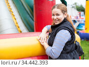 Toothy smiling mother stands leaning to inflatable jump castle, waits her children, outdoor portrait. Стоковое фото, фотограф Кекяляйнен Андрей / Фотобанк Лори