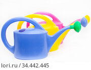 Blue, yellow and pink watering cans with shower nozzles, white background. Стоковое фото, фотограф Кекяляйнен Андрей / Фотобанк Лори