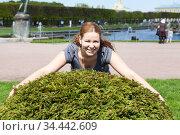 Smiling Caucasian woman trying to embrace green bushes in urban public park, looking at camera. Стоковое фото, фотограф Кекяляйнен Андрей / Фотобанк Лори