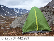 Green waterproof and windproof tent for hiking is in mountains at windy weather, standing behind big stone for protection from the wind, copyspace. Стоковое фото, фотограф Кекяляйнен Андрей / Фотобанк Лори