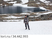 Adult man backpacker standing on snow patch while hiking in mountains, mountaineering with backpack, mountain lake landscape with glacier is on background. Стоковое фото, фотограф Кекяляйнен Андрей / Фотобанк Лори