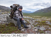 Adult Caucasian mountaineer resting on stone with heavy backpack on his back, man hiking in mountains, looking at camera, copyspace. Стоковое фото, фотограф Кекяляйнен Андрей / Фотобанк Лори