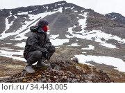 Caucasian teenager dressing warm waterproof hiking clothes for mountaineering, young man sitting on rock and looking far away in mountains. Стоковое фото, фотограф Кекяляйнен Андрей / Фотобанк Лори
