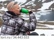 Portrait of Caucasian man drinking energy drink or coffee on the mountain peak, one climber or mountaineer in mountains. Стоковое фото, фотограф Кекяляйнен Андрей / Фотобанк Лори