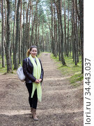 Full-length portrait of adult European woman dressing handkerchief and black leather jacket standing in pine wood on pathway with small backpack. Стоковое фото, фотограф Кекяляйнен Андрей / Фотобанк Лори