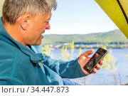 A mature man sits at the entrance to a tourist tent, looks at a smartphone against the background of a picturesque view of the Volga open spaces. Стоковое фото, фотограф Акиньшин Владимир / Фотобанк Лори