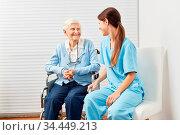 Alte Seniorin im Rollstuhl mit Frau vom Pflegedienst zu Hause bei... Стоковое фото, фотограф Zoonar.com/Robert Kneschke / age Fotostock / Фотобанк Лори