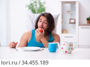 Young man waking up at home. Стоковое фото, фотограф Elnur / Фотобанк Лори