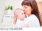 Liebende Mutter gibt ihrem Baby einen Kuss auf die Stirn. Стоковое фото, фотограф Zoonar.com/Robert Kneschke / age Fotostock / Фотобанк Лори