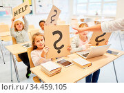 Kinder in Klasse von Grundschule halten Fragezeichen hoch als Problem... Стоковое фото, фотограф Zoonar.com/Robert Kneschke / age Fotostock / Фотобанк Лори