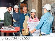 Arbeiter Team steht im Betrieb bei der Planung der Produktion zur... Стоковое фото, фотограф Zoonar.com/Robert Kneschke / age Fotostock / Фотобанк Лори