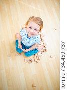Glückliches blondes Kind spielt mit Bausteinen auf dem Boden. Стоковое фото, фотограф Zoonar.com/Robert Kneschke / age Fotostock / Фотобанк Лори