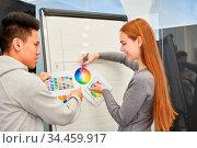 Kreativteam der Designagentur bespricht eine Idee zur Farbgestaltung... Стоковое фото, фотограф Zoonar.com/Robert Kneschke / age Fotostock / Фотобанк Лори
