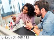 Afrikanische Frau als Webdesigner im Büro in Zusammenarbeit mit Grafikdesigner. Стоковое фото, фотограф Zoonar.com/Robert Kneschke / age Fotostock / Фотобанк Лори