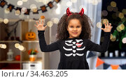 girl in black dress and devil's horns on halloween. Стоковое фото, фотограф Syda Productions / Фотобанк Лори