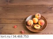 Спелые сочные персики в терракотовой тарелке на деревянном столе. Свободное место для текста. Стоковое фото, фотограф Наталья Гармашева / Фотобанк Лори