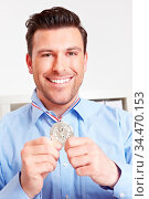 Glücklicher Mann im Büro mit Silbermedaille um den Hals. Стоковое фото, фотограф Zoonar.com/Robert Kneschke / age Fotostock / Фотобанк Лори