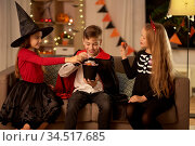 kids in halloween costumes share candies at home. Стоковое фото, фотограф Syda Productions / Фотобанк Лори