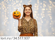 woman in halloween costume of leopard with pumpkin. Стоковое фото, фотограф Syda Productions / Фотобанк Лори
