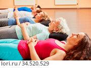Gruppe macht Meditation zur Entspannung nach dem Yoga Kurs. Стоковое фото, фотограф Zoonar.com/Robert Kneschke / age Fotostock / Фотобанк Лори