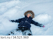 Little girl lying in a deep snow after heavy snowfall, moving her... Стоковое фото, фотограф Zoonar.com/Pawel Opaska / easy Fotostock / Фотобанк Лори