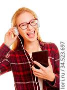 Lachende junge Frau mit Smartphone hört Musik über Kopfhörer. Стоковое фото, фотограф Zoonar.com/Robert Kneschke / age Fotostock / Фотобанк Лори