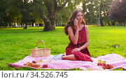 woman calling on smartphone on picnic at park. Стоковое видео, видеограф Syda Productions / Фотобанк Лори