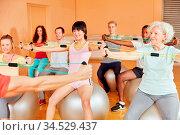 Gruppe mit einer Seniorin dehnt sich bei Kurs im Fitnesscenter. Стоковое фото, фотограф Zoonar.com/Robert Kneschke / age Fotostock / Фотобанк Лори