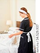 Zimmermädchen beim Housekeeping im Hotel bezieht das Bett. Стоковое фото, фотограф Zoonar.com/Robert Kneschke / age Fotostock / Фотобанк Лори
