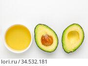 Avocado oil in a small ceramic bowl and two halfs of avacado fruit... Стоковое фото, фотограф Zoonar.com/Marek Uliasz / easy Fotostock / Фотобанк Лори