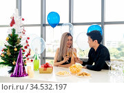 Young asian adult couple celebrating New year christmas holiday with... Стоковое фото, фотограф Zoonar.com/Vichie81 / easy Fotostock / Фотобанк Лори