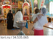 Godmother with her goddaughter on arms standing close to baptistery during baptism ceremony in Russian small church. Стоковое фото, фотограф Кекяляйнен Андрей / Фотобанк Лори