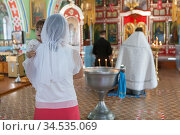People stand close to baptistery. It is sacrament of initiation into the Christian church. Godmother with goddaughter have ceremony of the Baptism of baby in the Orthodox church. Стоковое фото, фотограф Кекяляйнен Андрей / Фотобанк Лори