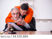 Old male judge meeting with young captive in courthouse. Стоковое фото, фотограф Elnur / Фотобанк Лори