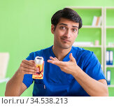 Young dentist practicing work on tooth model. Стоковое фото, фотограф Elnur / Фотобанк Лори
