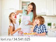 Zwei Kinder naschen beim Backen von Kuchen mit der Mutter in der Küche. Стоковое фото, фотограф Zoonar.com/Robert Kneschke / age Fotostock / Фотобанк Лори