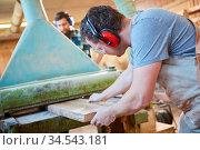 Schreiner oder Tischler schiebt eine Holz Bohle in eine Dickenhobelmaschine. Стоковое фото, фотограф Zoonar.com/Robert Kneschke / age Fotostock / Фотобанк Лори