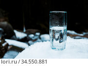A transparent glass glass with drinking mountain water stands in the... Стоковое фото, фотограф Zoonar.com/Ian Iankovskii / easy Fotostock / Фотобанк Лори
