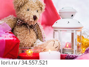 A close-up of a teddy bear with Christmas candles on a cozy checkered... Стоковое фото, фотограф Zoonar.com/Ian Iankovskii / easy Fotostock / Фотобанк Лори