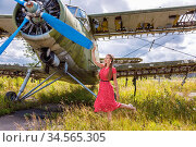 Cute young woman in a red pin up style dress standing by an abandoned green plane. Стоковое фото, фотограф Алексей Кузнецов / Фотобанк Лори