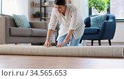 young woman unfolding carpet at home. Стоковое видео, видеограф Syda Productions / Фотобанк Лори