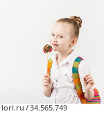 little schoolgirl with big knitted backpack eating delicious lollipop against a white background. Стоковое фото, фотограф Nataliia Zhekova / Фотобанк Лори