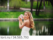 Young beautiful bride in a white dress with a bouquet standing near a pond. Стоковое фото, фотограф Nataliia Zhekova / Фотобанк Лори