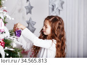 Little girl decorating christmas tree with toys and flowers. Стоковое фото, фотограф Nataliia Zhekova / Фотобанк Лори