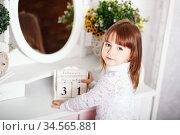 cute little girl sitting near a mirror with wooden calendar in his hands in anticipation of the new year. Стоковое фото, фотограф Nataliia Zhekova / Фотобанк Лори