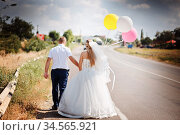 Happy married couple with balloons walk together on the road. Стоковое фото, фотограф Nataliia Zhekova / Фотобанк Лори