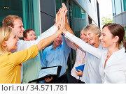 Erfolgreiches Business Team beim High Five geben vor dem Büro. Стоковое фото, фотограф Zoonar.com/Robert Kneschke / age Fotostock / Фотобанк Лори