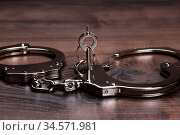 Handcuffs and keys on the brown wooden table background. Стоковое фото, фотограф Zoonar.com/Ruslan Ropat / age Fotostock / Фотобанк Лори