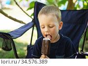 Adorable little boy eating ice cream pops in home's garden. Стоковое фото, фотограф Nataliia Zhekova / Фотобанк Лори