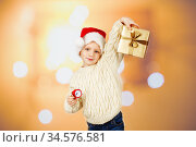 A little boy in a santa hat and in a warm knitted sweater holds a gift in a box and a small red alarm clock. We celebrate the New Year. Стоковое фото, фотограф Nataliia Zhekova / Фотобанк Лори